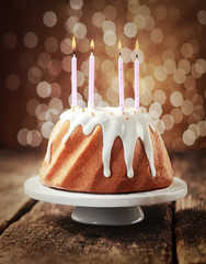 Birthday cake with four burning candles