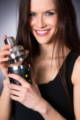 Young Attractive Female Bartender Smiling Mixes Martini Drink