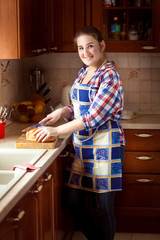 smiling woman cutting bread on wooden cutting board