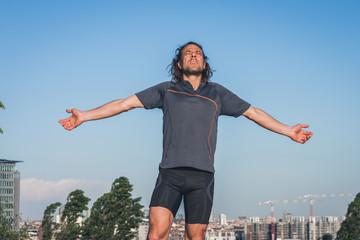 Portrait of a long haired athlete against blue sky