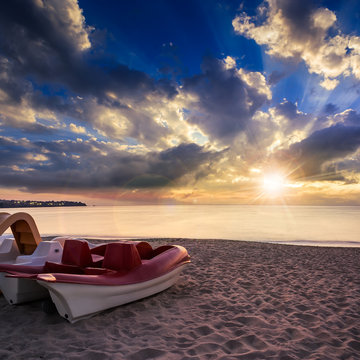 calm sea beach with boats at sunset