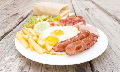 American  breakfast with fried eggs, bacon, sausages, toasts and