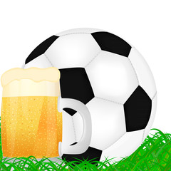 mug of beer and a soccer ball on green grass