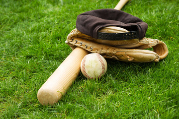 Old Baseball Equipment on Grass Field