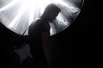 Junger Mann im Studio mit Blitzanlage und Schirm