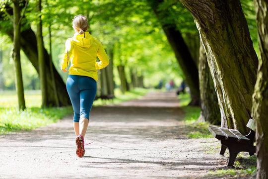 Woman runner running jogging in summer park