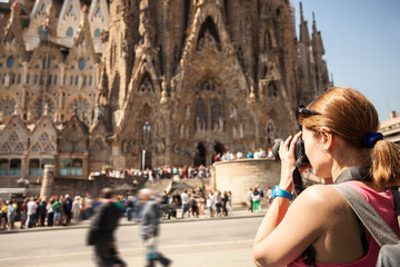 Young woman taking picture of Sagrada Familia, Barcelona, Spain