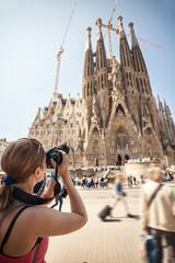 Young woman taking picture of Sagrada Familia, Barcelona, Spain