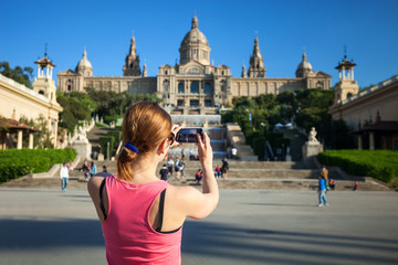 Young woman taking picture of Catalan National Art Museum