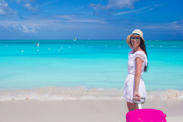 Young beautiful woman with colorful luggage on tropical beach