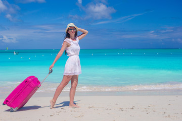 Young beautiful woman walking with her bag on tropical beach