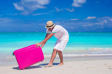 Young traveler with his luggage on a tropical beach