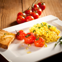 Scrambled eggs with roasted cherry tomatoes, toast and chive
