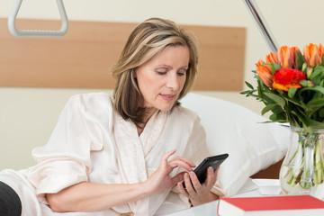 patientin im krankenhaus tippt auf ihrem smartphone