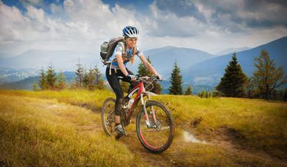 Woman mountain-bike riding on ridge with Carpatian Mountains
