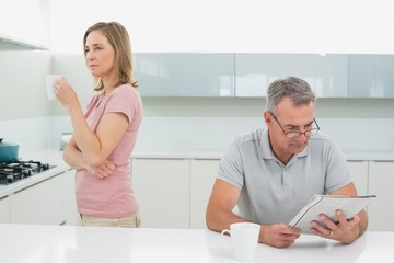 Displeased woman drinking coffee while man reading newspaper in