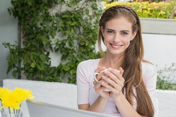 Beautiful woman with coffee and laptop at café