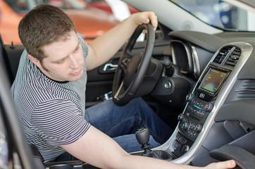 Man examining new car at the dealership.