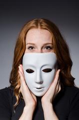 Redhead woman iwith mask in hypocrisy consept against grey backg