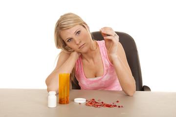 woman pink tank top pills look sad
