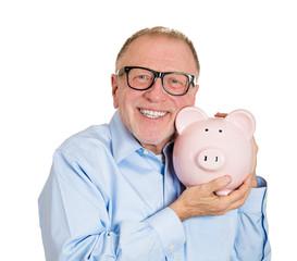 Savings in old age. Happy senior man holding piggy bank