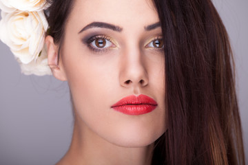 Beautiful woman with flowers in head professional make up