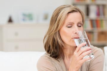 ältere attraktive frau trinkt ein glas wasser