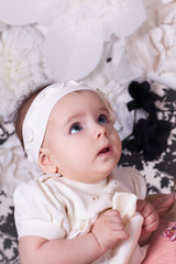 Girl 6 months white dress looks up in surprise