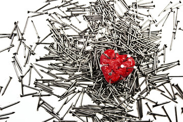 Red heart on pile of iron nails, pierced by a nails