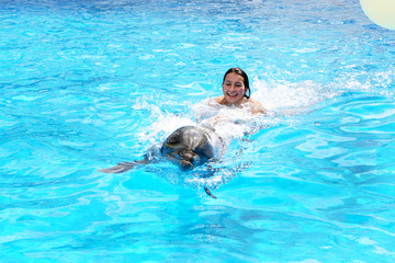 Foto op Canvas Dolfijnen Happy beautiful young girl laughs and swims with dolphins in blu