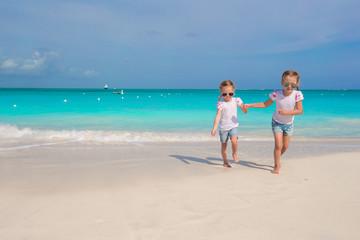 Little girls running along the white beach and having fun
