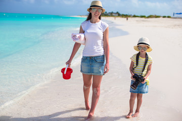 Little girl with camera and young mother walking at beach