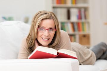 lächelnde frau mit roter brille liest ein buch