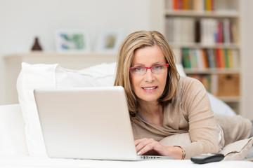 ältere attraktive frau mit laptop zu hause
