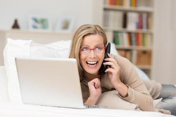frau mit laptop und telefon freut sich