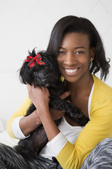 A young girl smiling, holding her small black pet dog.