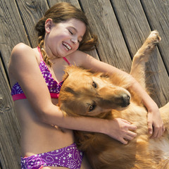 A girl in a bikini lying beside a golden retriever dog, viewed from above.