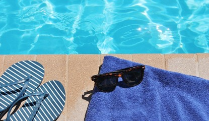 Poolside sunglasses towel holiday vacation background scenic sunglasses shoes with copy space on swimming pool water for vacation or holiday stock photo photograph image