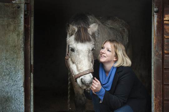 A woman standing next to a grey horse stroking its muzzle, at the stable door.