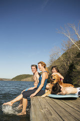A family and their retriever dog on a jetty by a lake.
