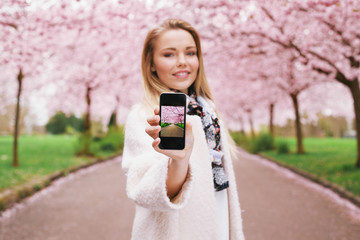 Young woman showing spring park picture on her mobile phone
