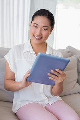 Smiling woman sitting on couch using tablet pc