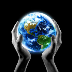 Hands holding Earth with a black background.