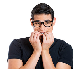 Nerdy anxious guy with glasses biting his fingernails