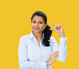Woman showing small size hand gesture on yellow background