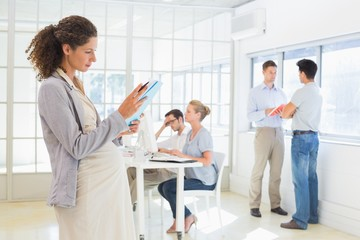 Pregnant businesswoman reading file with team behind her