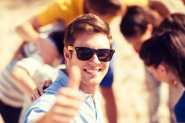 man with friends on the beach showing thumbs up