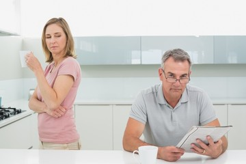 Woman drinking coffee while man reading newspaper in kitchen