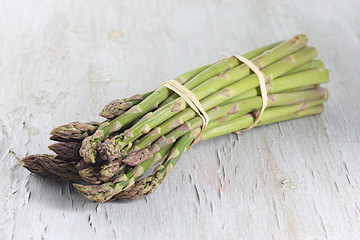 Delicious fresh green asparagus on grey wooden table