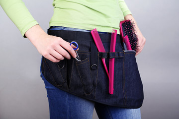 Woman hairdresser with tool belt on grey background